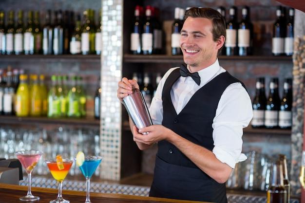 Barmixer, der ein cocktailgetränk im mixbecher mischt