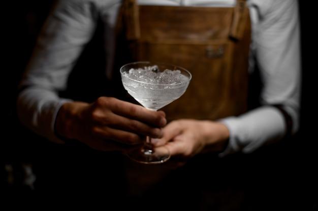Barmixer, der ein cocktailglas voll vom zerquetschten eis hält