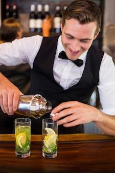 Barmixer, der ein getränk von einem schüttel-apparat zu einem glas auf stabkostenzähler gießt