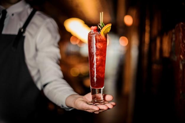 Barmixer, der ein glas des frischen sommerschustercocktails verziert mit erdbeere und minze hält