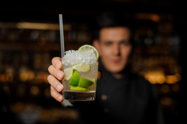 Barmixer, der ein glas mit einem frischen mojito hält