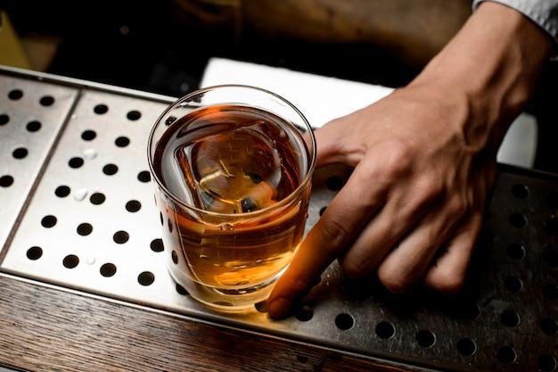 Barmixer, der ein goldenes cocktail im glas mit einem gestempelten großen eiswürfel dient