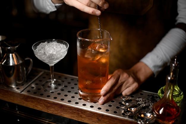 Barmixer, der ein köstliches braunes cocktail in der messenden glasschale rührt