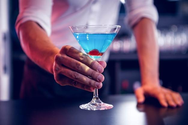 Barmixer, der einen blauen martini in der stange dient