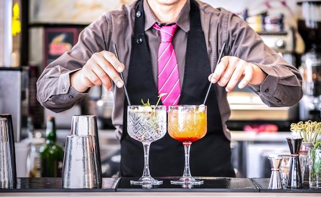Barmixer, der gin tonic und tequila-sonnenaufgang an der cocktailbar dient
