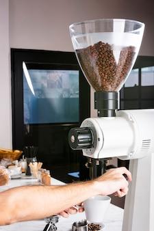 Barmixer, der kaffeegetränk an der kaffeemaschine zubereitet