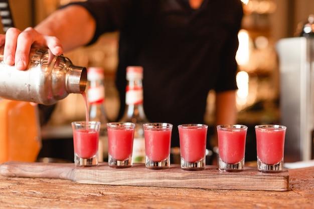 Barmixer, der rote cocktails in kleine gläser vom mixbecher setzt.