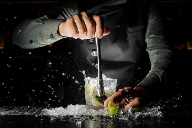 Barmixerhand, die frischen saft vom kalk macht caipirinha-cocktail zusammendrückt