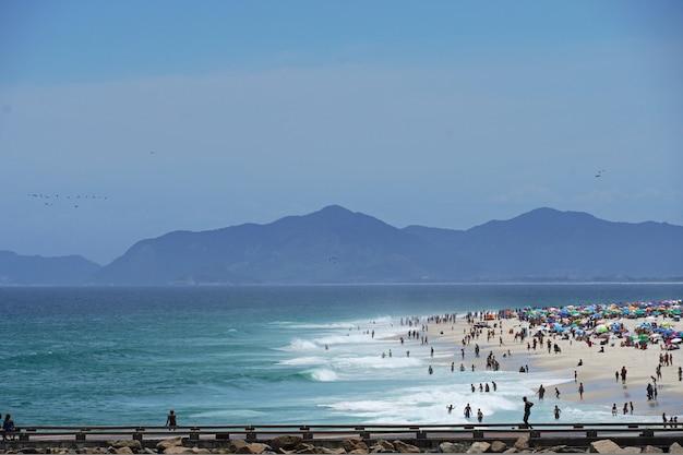 Barra da tijuca strand an einem sonnigen tag mit leuten, die den sand und das meer genießen. blick auf den wellenbrecher, den barra-kanal und den praia dos amores. rio de janeiro, rj, brasilien. februar 2021.