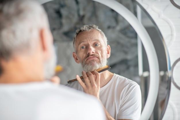 Bart stylen. ein mann kämmt seinen bart mit einem kamm