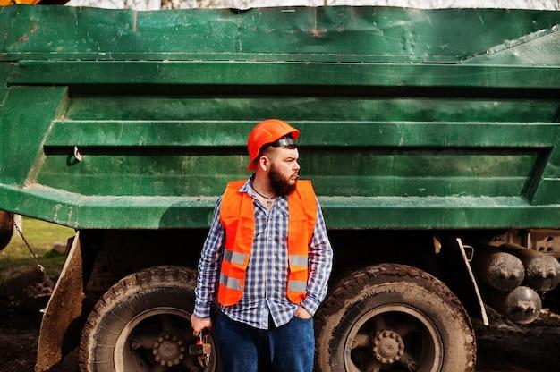 Bartarbeitskraftmannklagenbauarbeiter im orange sturzhelm der sicherheit, gegen kipper mit dem hammer und justierbarem schlüssel zur hand.