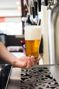 Bartenders hand, die großes bierglas unter dem vorsprung hält