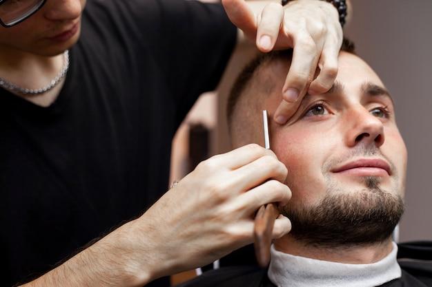 Barthaarschnitt in einem friseurladen, ein junger mann, der seinen bart mit einem rasiermesser rasiert, nahaufnahme
