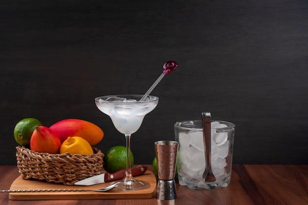 Bartheke, glas cocktail und etwas obst auf einem weidenkorb, eiskübel und messer,