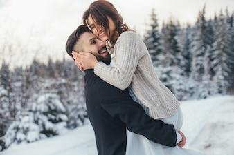 Bärtiger Mann und seine reizende Braut werfen auf dem Schnee in einem magischen Winterwald auf
