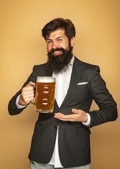 Bartmann, der bier von einem bierkrug trinkt. glücklicher lächelnder mann mit bier. senior mann, der bier mit trinkt