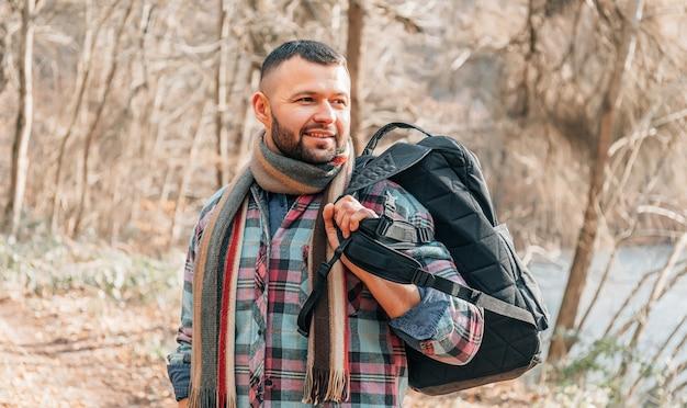 Bartmann im park. junger reisender im wald. einsamer mann mit rucksack und jacke. erwachsener ernster mann mit schwarzem bart im herbstpark.