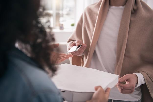 Barzahlung. nahaufnahme einer kreditkarte, die dem kurier beim bezahlen der pizza gegeben wird