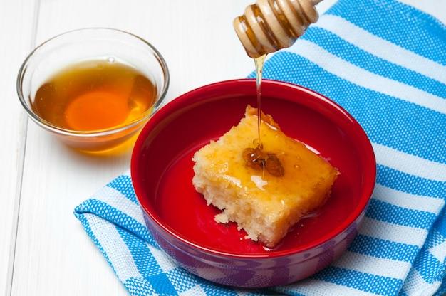 Basbousa - arabischer kuchen mit mandeln und honigsirup in der schüssel auf weißem hölzernem