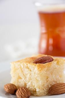 Basbousa traditioneller arabischer grieß-kuchen mit nuss-orangenblüten-wasser-vertikalem kopienraum weißhintergrund