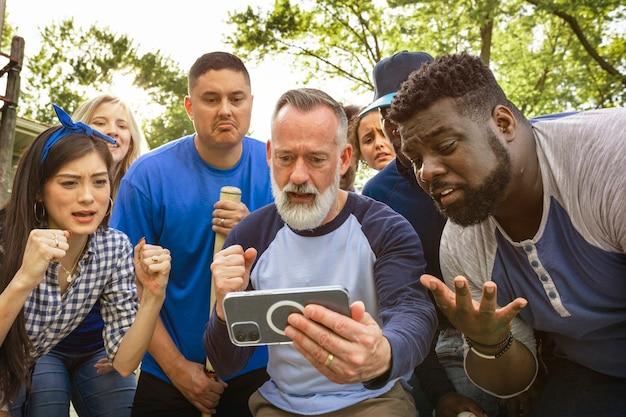 Baseball-fans sehen ihrem team beim verlieren des spiels auf einem telefon zu