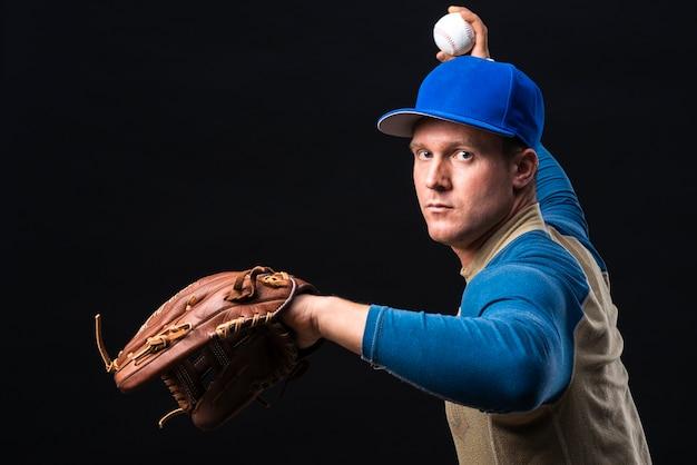 Baseball-spieler mit werfender kugel des handschuhs