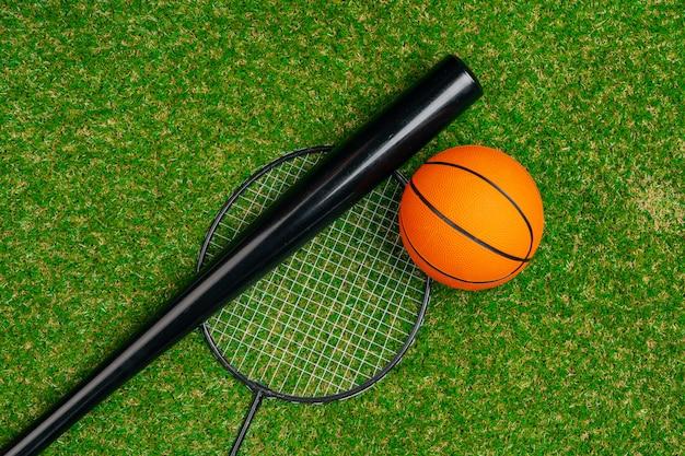 Baseballschläger und federballschläger auf gras, draufsicht