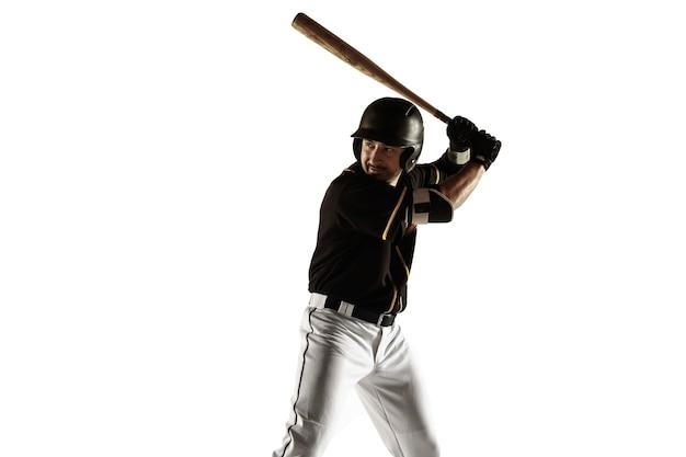 Baseballspieler, krug in einer schwarzen uniform, die auf einer weißen wand übt und trainiert. junger berufssportler in aktion und bewegung. gesunder lebensstil, sport, bewegungskonzept.