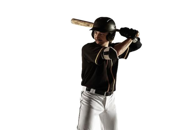 Baseballspieler, krug in einer schwarzen uniform, die lokalisiert auf einer weißen wand übt und trainiert. junger profisportler in aktion und bewegung. gesunder lebensstil, sport, bewegungskonzept.