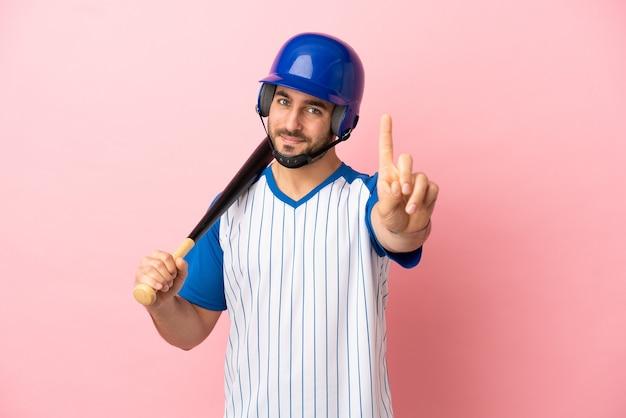 Baseballspieler mit helm und schläger einzeln auf rosa hintergrund, der einen finger zeigt und hebt