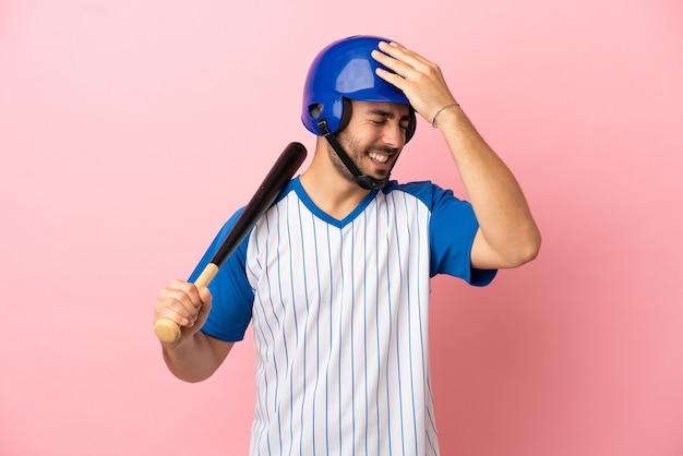 Baseballspieler mit helm und schläger einzeln auf rosa hintergrund hat etwas erkannt und beabsichtigt die lösung