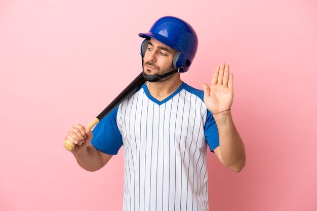 Baseballspieler mit helm und schläger einzeln auf rosafarbenem hintergrund, der stoppgeste macht und enttäuscht