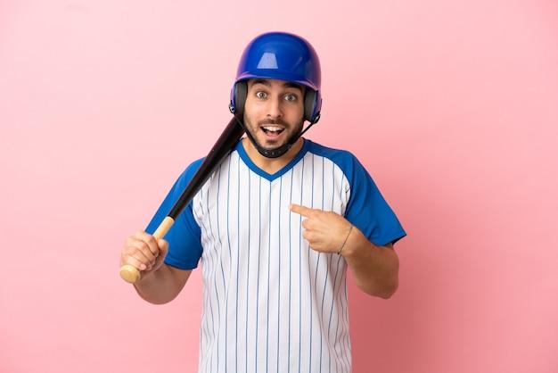 Baseballspieler mit helm und schläger einzeln auf rosafarbenem hintergrund mit überraschendem gesichtsausdruck