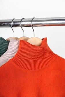 Basic herbst damen kleiderschrank konzept leere rollkragenpullover auf kleiderbügel leuchtend orange ocker...