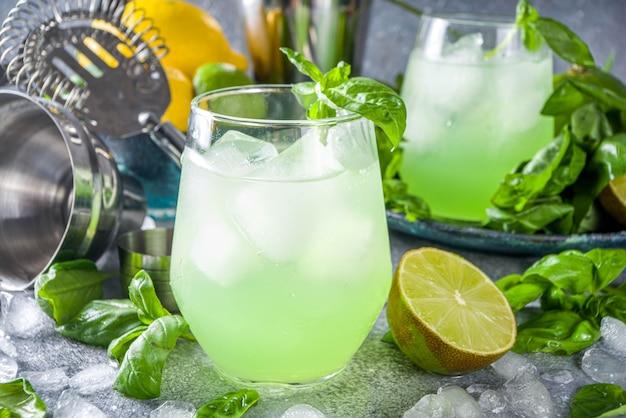 Basil smash gin alkoholischer cocktail. langes alkoholgetränkrezept mit frischen basilikumblättern und limetten, grauer steinhintergrundkopierraum