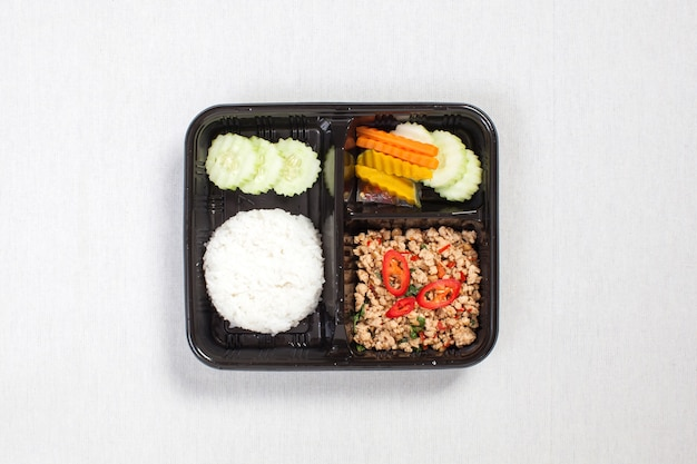 Basilikum gebratener reis mit gehacktem hühnchen, in eine schwarze plastikbox gelegt, auf eine weiße tischdecke gelegt, lebensmittelbox, würziges gebratenes hühnchen mit basilikumblättern, thailändisches essen.