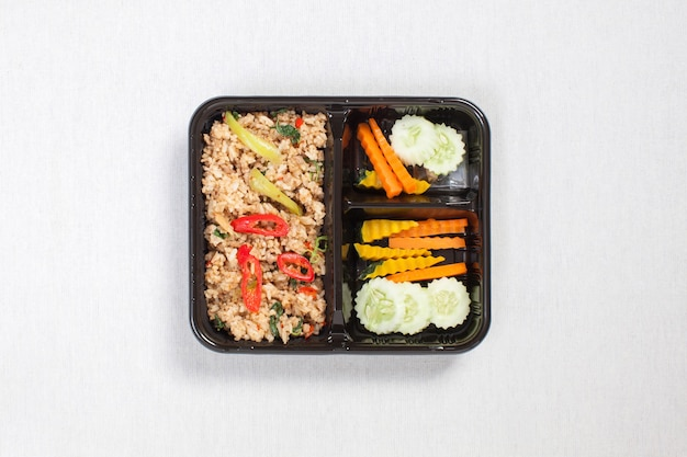 Basilikum gebratener reis mit gehacktem schweinefleisch, in eine schwarze plastikbox gelegt, auf eine weiße tischdecke gelegt, lebensmittelbox, würzig gebratenes schweinefleisch mit basilikumblättern, thailändisches essen.