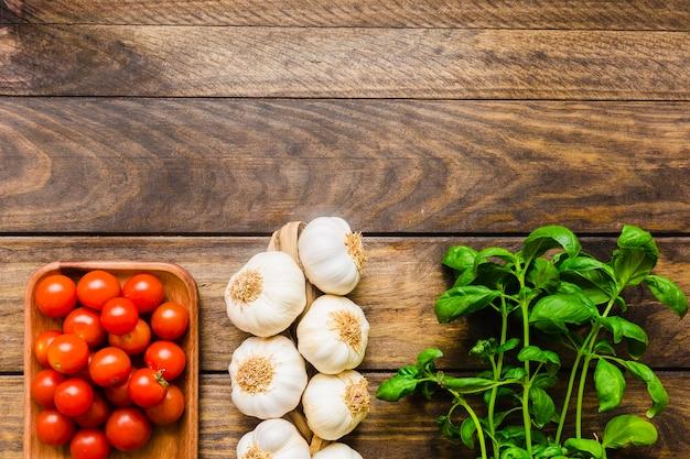 Basilikum in der nähe von knoblauch und tomaten