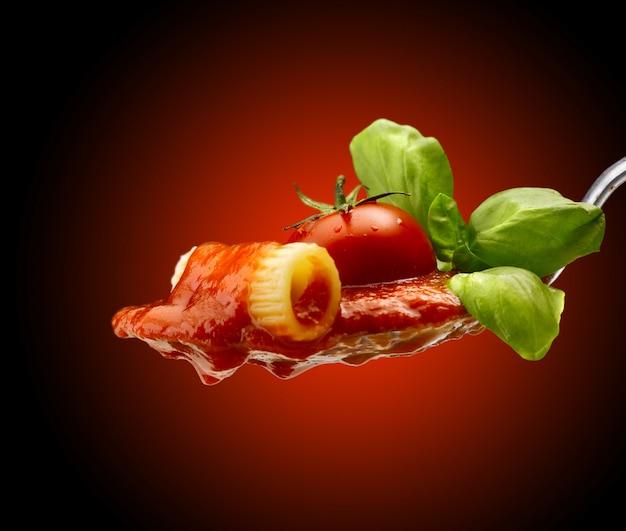 Basilikum in der nähe von nudeln und tomatensauce in einem löffel