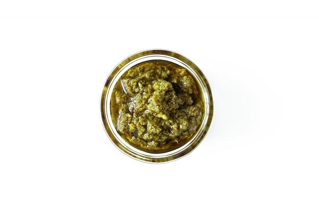 Basilikum italienische pesto-soße in der glasschale lokalisiert auf weißem hintergrund