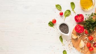 Basilikumblätter; Chiasamen; halbierte Tomaten und Öl auf weißem Holzfußboden angeordnet