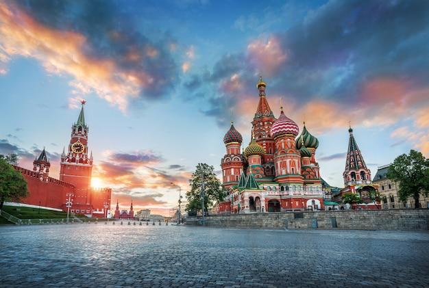 Basilius-kathedrale und der spasskaya-turm in moskau unter sonnenuntergangswolken