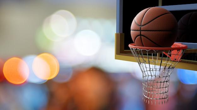 Basketball, der in band auf schönem bokeh des bunten stadionhellhintergrundes einsteigt