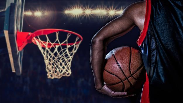 Basketball-spieler mit einem ball auf dunklem hintergrund