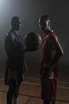 Basketball-spieler zwei, der einen einzelnen basketball hält