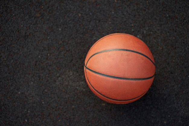 Basketballball auf dem schwarzen hintergrund des straßengerichts im freien