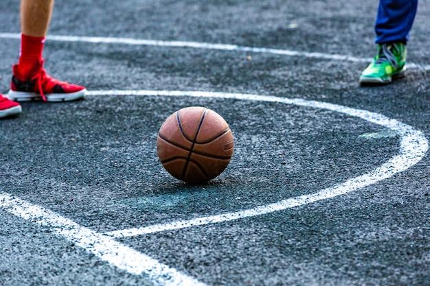 Basketballball im außenplatz, der auf dem boden liegt
