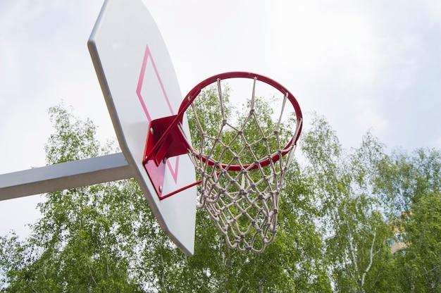 Basketballkorb im park auf bäumen eines hintergrundgrüns