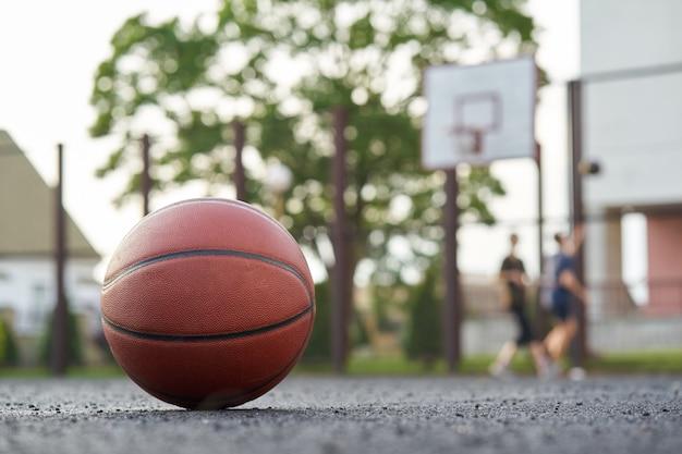 Basketballkugel auf den straßengerichtspielern im freien spielt ein spiel auf dem hintergrund