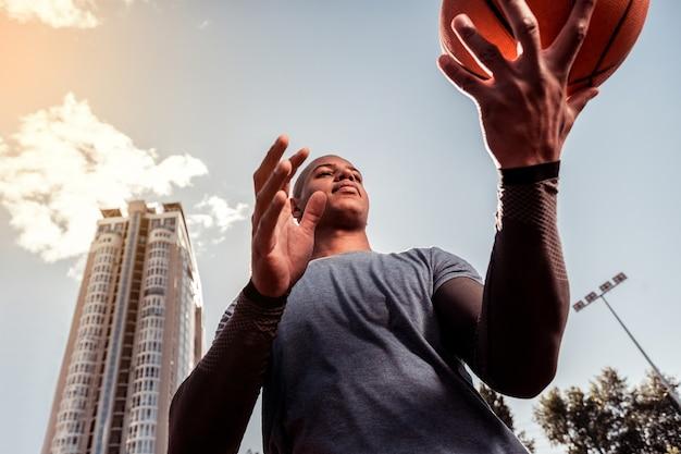 Basketballliebhaber. ernsthafter junger mann, der den ball in seinen händen betrachtet, während er mit ihm trainiert